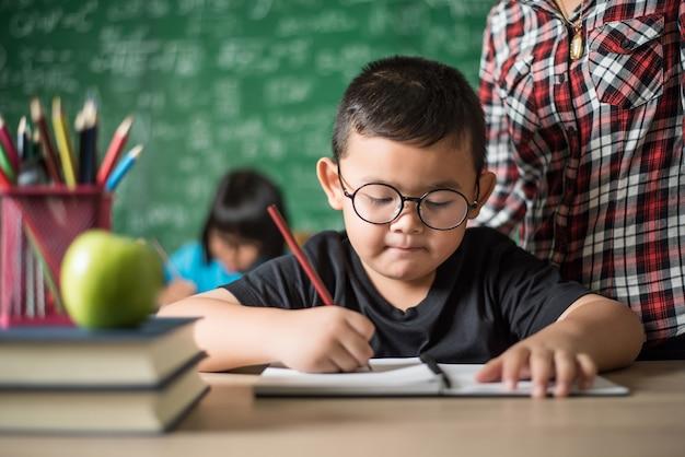 Garoto escreve um livro na sala de aula.