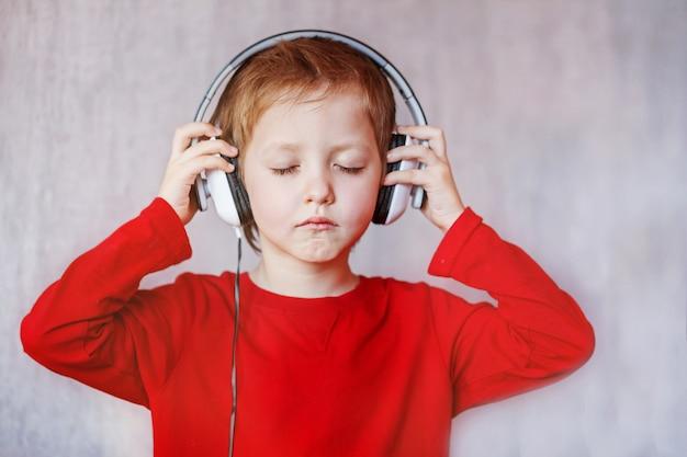 Garoto escuta música em casa. criança com fones de ouvido.