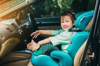 Garoto espere por mãe e sente-se no banco do carro para a segurança antes de ir para a escola.
