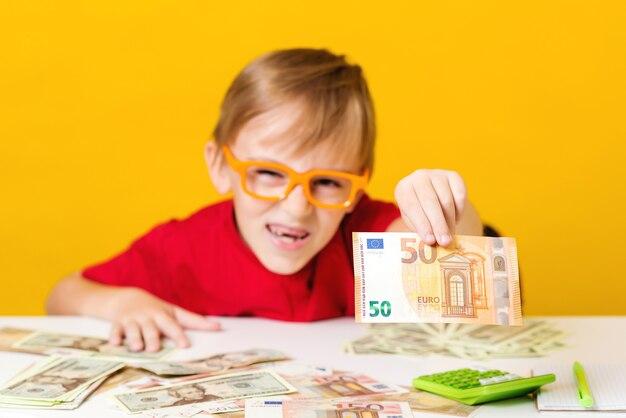 Garoto esperto de óculos com dinheiro em espécie. criança pensando onde investir dinheiro.