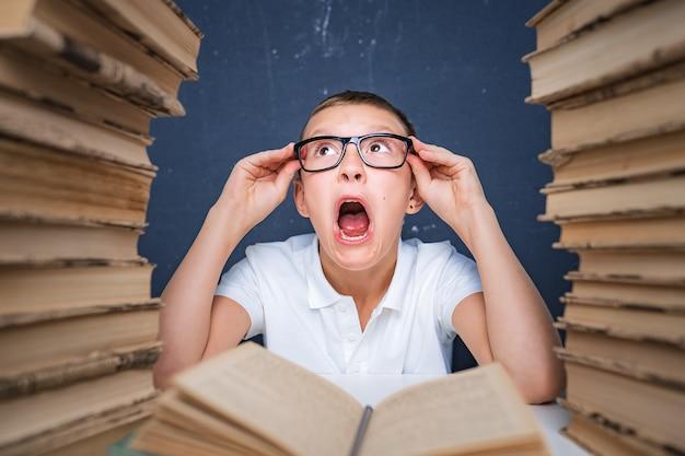 Garoto esperto de óculos ficando louco de ler livro sentado entre duas pilhas de livros