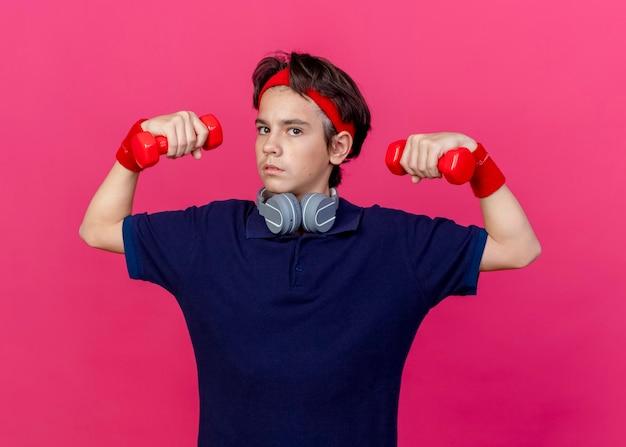 Garoto esportivo bonito e confiante usando bandana e pulseiras e fones de ouvido no pescoço com aparelho dentário levantando halteres olhando para frente isolado na parede rosa