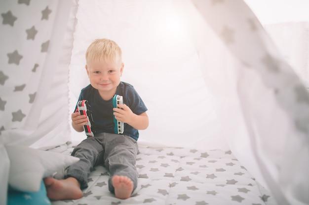 Garoto está deitado no chão. o menino está jogando em casa com carros de brinquedo em casa pela manhã. estilo de vida casual no quarto.