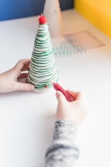 Garoto está mostrando uma decoração da árvore de natal. fabricação de árvore de natal artesanal criativa. conceito de diy infantil. fazendo decoração de brinquedos de natal. decore o brinquedo com strass. árvore de natal ecológica