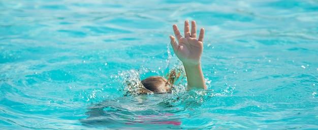 Garoto está se afogando no mar.