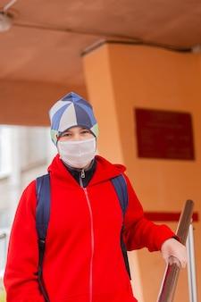Garoto estudante sai da escola usando máscara protetora