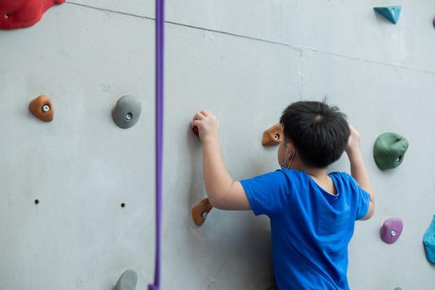 Garoto fazendo escalada indoor