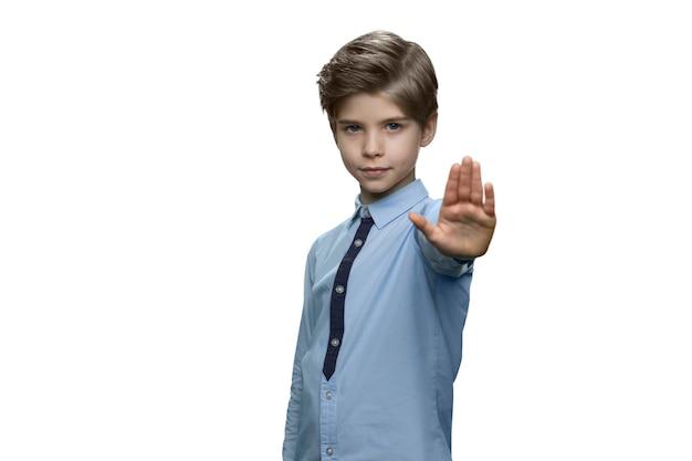 Garoto fazendo gesto de parada com a palma da mão na parede branca Foto Premium