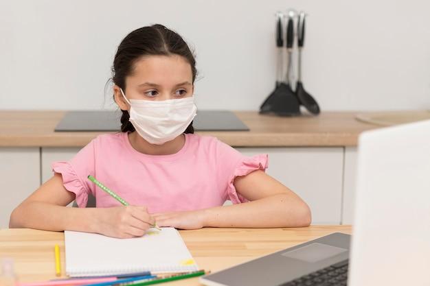 Garoto fazendo lição de casa com máscara