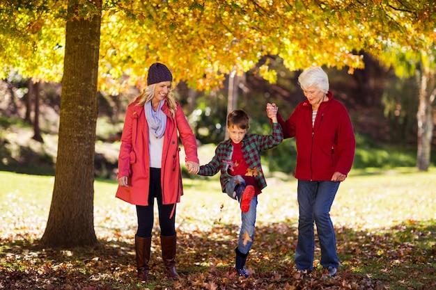Garoto feliz andando com a mãe e a avó