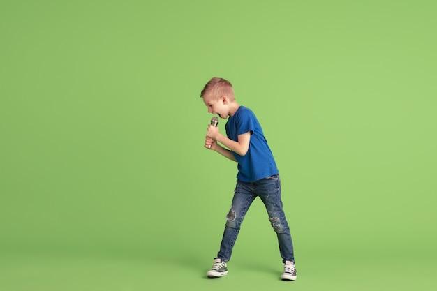 Garoto feliz brincando e se divertindo na parede verde do estúdio