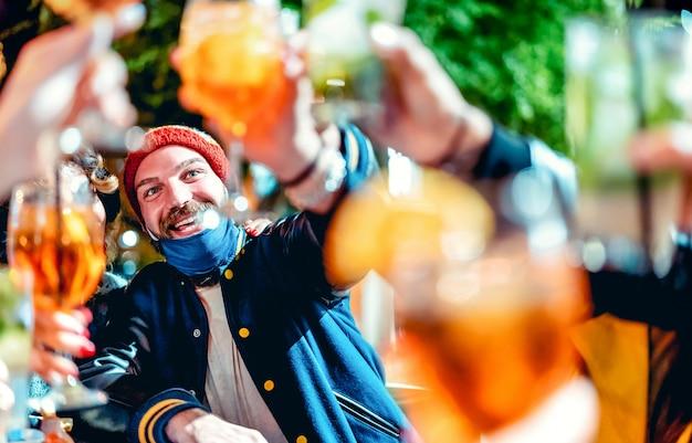 Garoto feliz brindando bebidas chiques em bar noturno com máscara aberta