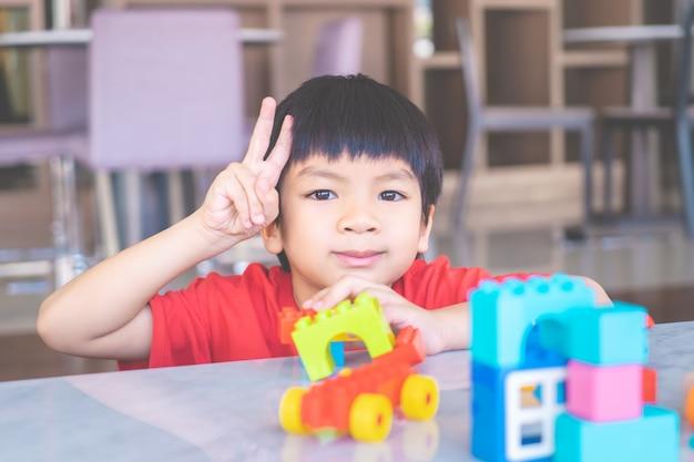 Garoto feliz, cercado por blocos de brinquedo colorido vista superior forma v mão para vitória