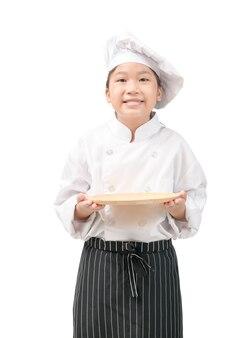 Garoto feliz chef de uniforme segurando o prato vazio isolado no branco