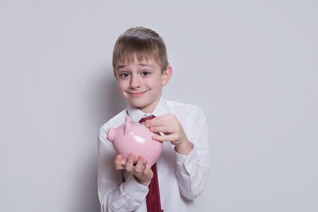 Garoto feliz coloca uma moeda em um cofrinho rosa. conceito de negócios. luz de fundo