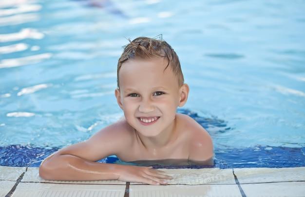 Garoto feliz com cabelos loiros sorrindo sentado na piscina