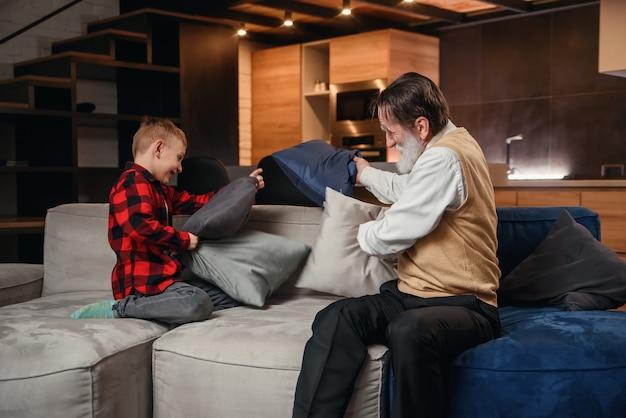 Garoto feliz com engraçado vovô moderno lutando com almofadas se divertindo juntos, sentado no sofá confortável em casa.