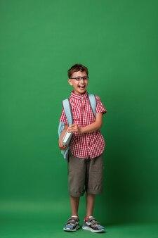 Garoto feliz com óculos com uma mochila e um livro