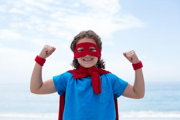 Garoto feliz em traje de super-heróis, flexionando os músculos na beira-mar