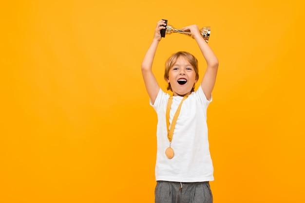 Garoto feliz em uma camiseta com uma medalha no pescoço levanta a taça do vencedor em amarelo com espaço de cópia