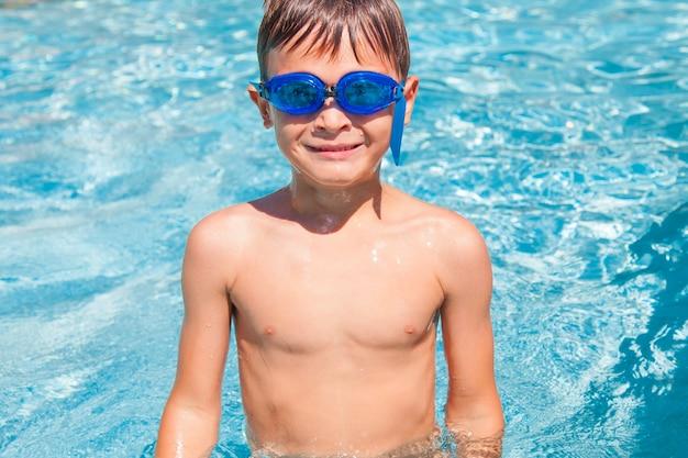 Garoto feliz em uma piscina. garoto menino bonitinho se divertindo em uma piscina. ao ar livre. atividades esportivas para crianças.