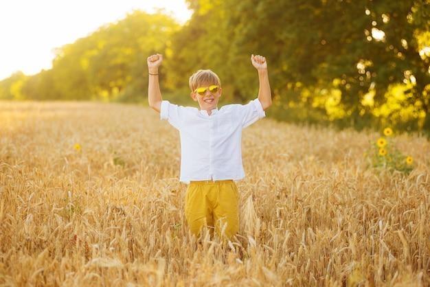 Garoto feliz está fazendo o gesto forte e vencedor em pé em um campo.