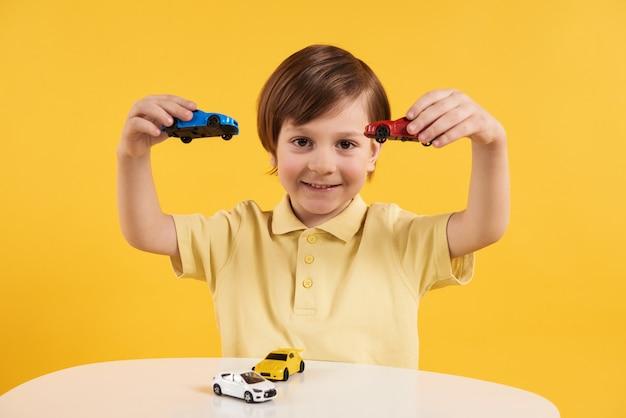 Garoto feliz está jogando carros de brinquedo. conceito de lazer de crianças.