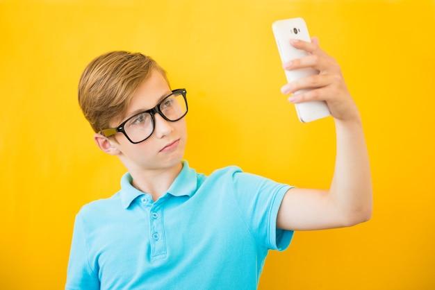 Garoto feliz fazendo selfie em fundo amarelo