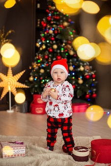 Garoto feliz, garoto com chapéu vermelho do papai noel, pijama fica com decoração de natal