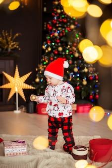 Garoto feliz, garoto no chapéu vermelho do papai noel com decorações de natal