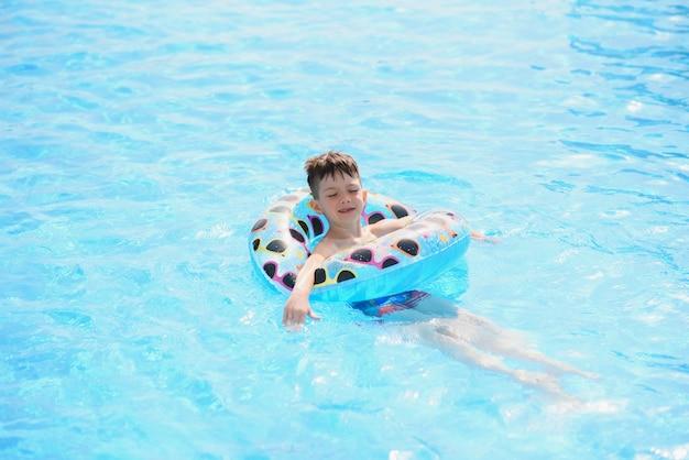Garoto feliz na piscina. o menino está sozinho, nadando em um ringue inflável e rodeado por respingos de água.