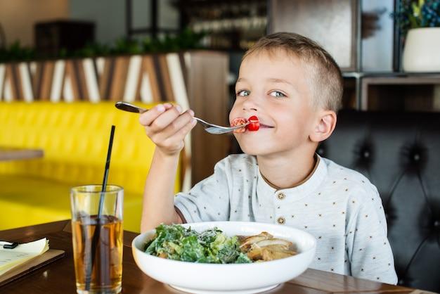 Garoto feliz no café comendo uma salada