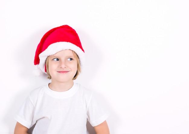 Garoto feliz no chapéu de papai noel vermelho. conceito de natal