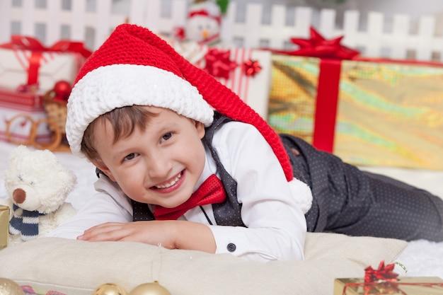 Garoto feliz no interior de natal, chapéu de papai noel com presentes