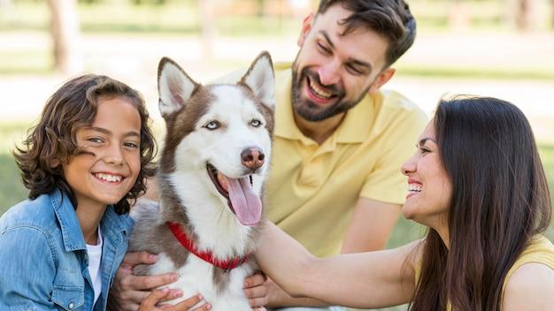 Garoto feliz posando no parque com o cachorro e os pais