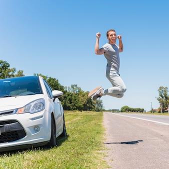 Garoto feliz pulando na estrada ao lado do carro