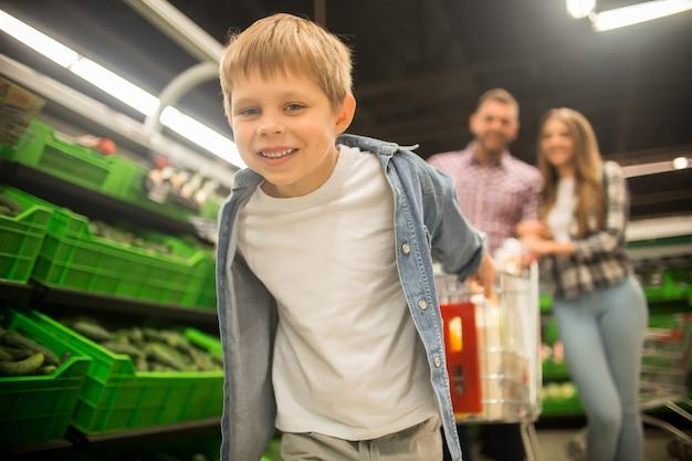 Garoto feliz, puxando o carrinho no supermercado