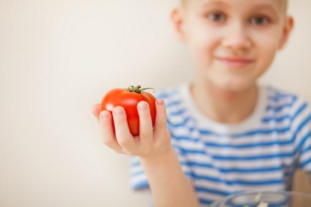 Garoto feliz, segurando legumes de tomate