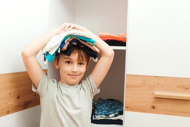 Garoto feliz segurando uma pilha de roupas na cabeça. garoto organizando roupas no guarda-roupa.