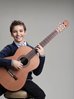 Garoto feliz tocando violão.