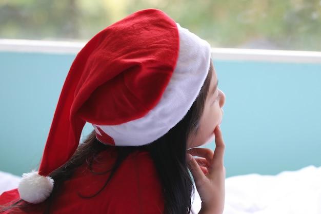 Garoto feminino bonito usando chapéu de papai noel pensando em comida doce de lição de casa ou doces