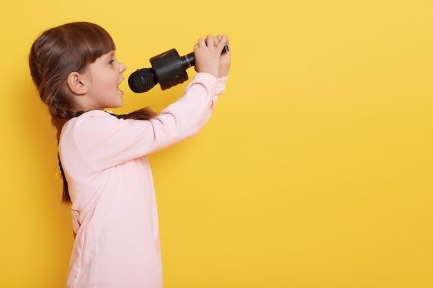 Garoto feminino encantador talentoso com rabo de cavalo cantando canções no microfone, perfil da pequena artista posando isolado sobre a parede amarela, copie o espaço.