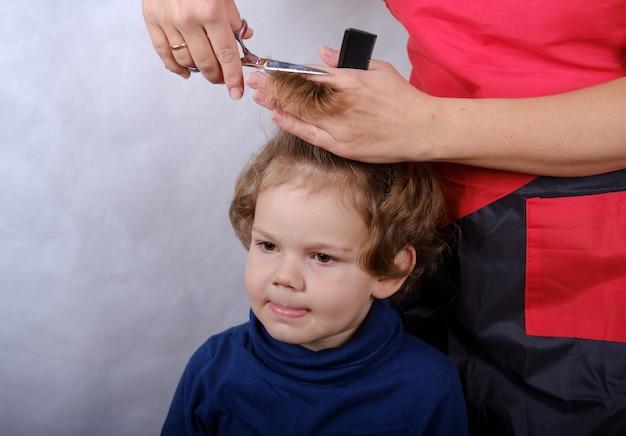 Garoto fofo, aparência europeia durante o corte de cabelo com tesoura