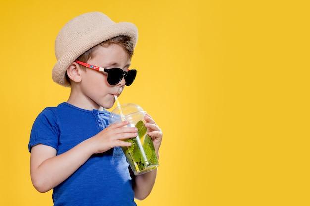 Garoto fofo bebe coquetel de mojito em copo de plástico sobre fundo amarelo