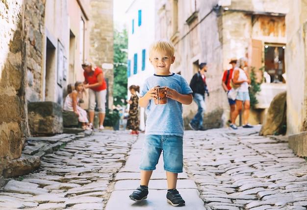 Garoto fofo com bolinhos caseiros fritule com chocolate em uma rua da cidade da croácia