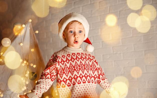 Garoto fofo com chapéu de papai noel brincando na sala, garoto desembrulhando presentes