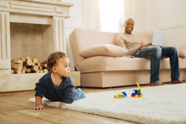 Garoto fofo. menino doce de olhos escuros rastejando no chão e brincando com seus brinquedos enquanto seu pai está sentado no sofá com seu laptop ao fundo