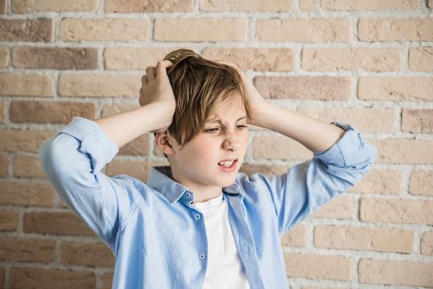 Garoto frustrado está arrancando os cabelos. frustração, depressão, conceito de problemas parentais