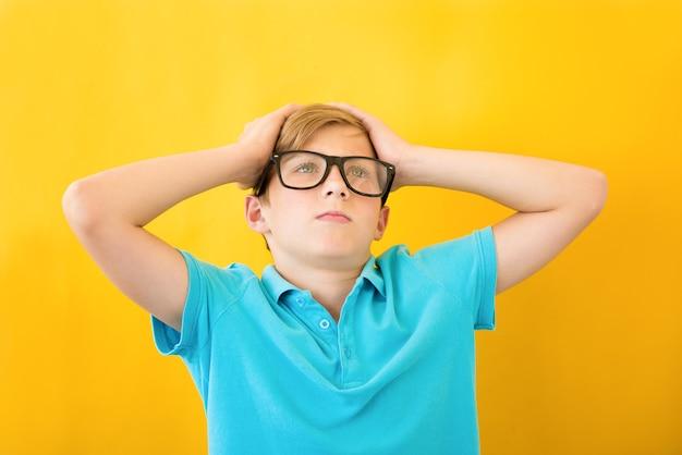 Garoto frustrado segurando sua cabeça em um fundo amarelo. conceito de estudo, dificuldades e problemas