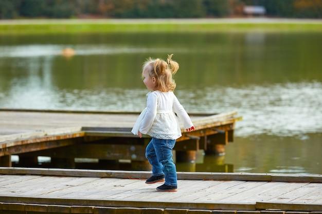 Garoto garota andando no cais do lago